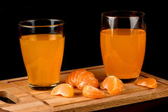 Juice in a glass and peeled tangerine closeup Stock Photo