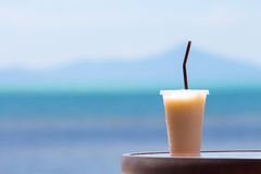 Juice. A glass of juice on the table with the sea as a background Royalty Free Stock Photography