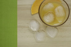 Juice with ice. A glass of juice with ice is on a wooden table Royalty Free Stock Photos