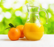Jug of orange juice on nature background Royalty Free Stock Photo
