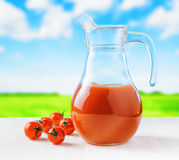 Jug of tomato juice on nature background Stock Photography