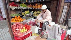Juice maker in fruit shop. AGRA, UTTAR PRADESH, INDIA - FEBUARY 24, 2015: Muslim man making fresh carrot juice in his shop on the Taj Ganj Street stock video