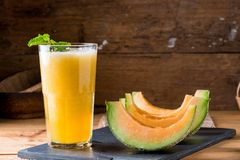 The juice of melon with mint in a glass on the table. Hami melon stock photo