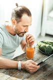 Focused unshaken man sitting and using the tablet. Juice and news. Focused unshaken serious man sitting the spacious room drinking fresh juice and using the Royalty Free Stock Photo