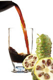 Juice from Noni fruit flowing into cocktail glass Royalty Free Stock Photography