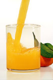 Juice with orange. Fresh juice being poured into a glass with a whole orange behind Royalty Free Stock Images