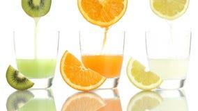 Juice orange lemon kiwi poured into glass. On white background stock video