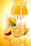 Juice pitcher, Oranges with leaves on yellow backgr Royalty Free Stock Image