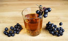 Juice of rowanberry in cup on table. Juice of rowanberry in cup on wooden table with branch of rowanberry Stock Photos