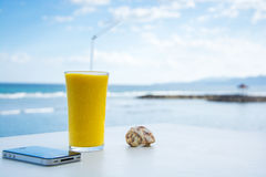 Juice on the table. Mango juice, phone and shell on the table Stock Photo