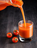 Tomato juice pouring from jug into a glass Royalty Free Stock Images