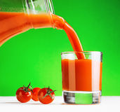 Tomato juice pouring from jug into a glass Stock Photos