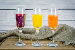Juice variations on a wooden table Royalty Free Stock Images