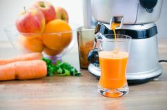 Juicer and carrot juice Royalty Free Stock Photography