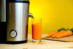 Juicer and carrot juice in glass Stock Photo