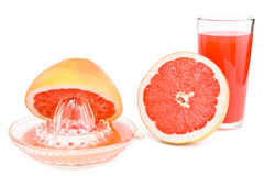 Juicer, cut a grapefruit and a glass of juice. Juicer, cut a grapefruit and a glass of juice are isolated on the white Royalty Free Stock Photography