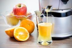 Juicer e suco de laranja fotografia de stock royalty free
