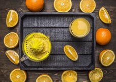 Juicer and a glass of juice with sliced oranges in a wooden tray wooden rustic background top view close up Stock Photography