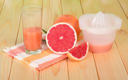 Juicer, grapefruit juice in glass, whole fruit and slices Royalty Free Stock Photo