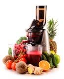 Juicer lento con las frutas y verduras orgánicas en blanco Imagenes de archivo