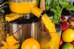 Juicer lento na cozinha com muitos do suco alaranjado da vitamina das frutas e legumes fundo saudável do conceito do estilo de vi imagem de stock royalty free