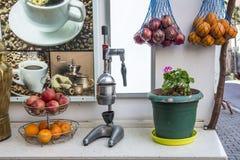 Juicer manual con las manzanas y las naranjas del granate imagen de archivo