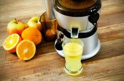 Juicer och orange fruktsaft Arkivfoto