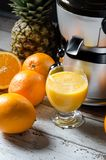 Juicer and orange juice in glass on wooden desk Royalty Free Stock Photo