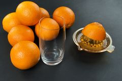 Juicer with oranges. Manual juicer with oranges on dark background royalty free stock photo