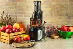 Juicer und Apfelsaft Zubereitung von gesunden frischen Säften Juicing Hauptäpfel in der Küche Verarbeitung der herbstlichen Fruch stockfotos