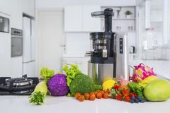 Juicer with various fruits and vegetables in kitchen Royalty Free Stock Photos