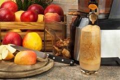 Juicer y zumo de manzana Preparación de los jugos frescos sanos Manzanas juicing caseras en la cocina Proceso de la fruta otoñal fotografía de archivo