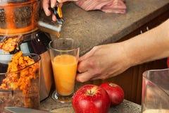 Juicer y zumo de manzana Preparación de los jugos frescos sanos Manzanas juicing caseras en la cocina Proceso de la fruta otoñal fotos de archivo