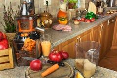 Juicer y zumo de manzana Preparación de los jugos frescos sanos Manzanas juicing caseras en la cocina Proceso de la fruta otoñal imagen de archivo