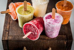 Juices and smoothie popsicles. Healthy summer desserts. Ice cream popsicles. Frozen tropical juices, smoothies blueberries. currants, orange, mango, kiwi, banana Royalty Free Stock Images