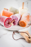 Juices and smoothie popsicles. Healthy summer desserts. Ice cream popsicles. Frozen tropical juices, smoothies blueberries. currants, orange, mango, kiwi, banana Stock Images