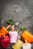 Juices and smoothie popsicles. Healthy summer desserts. Ice cream popsicles. Frozen tropical juices, smoothies blueberries. currants, orange, mango, kiwi, banana Stock Photo