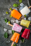 Juices and smoothie popsicles. Healthy summer desserts. Ice cream popsicles. Frozen tropical juices, smoothies blueberries. currants, orange, mango, kiwi, banana Royalty Free Stock Photography