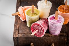 Juices and smoothie popsicles. Healthy summer desserts. Ice cream popsicles. Frozen tropical juices, smoothies blueberries. currants, orange, mango, kiwi, banana Stock Image