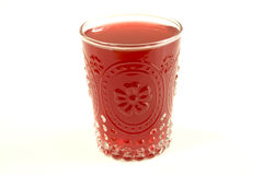 Juices on a white background. Red juice in a glass with flower pattern on a white background Stock Images