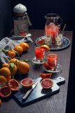Juicing Blood Oranges to Make Orange Juice. The ingredients and kitchen tools for making orange juice are on a wooden table in a dark kitchen. Sicilian blood Stock Images