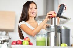 Juicing - kvinnadanandeäpple och grönsakfruktsaft Arkivfoton