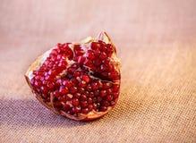 Juicy γλυκό ρόδι φετών στο υπόβαθρο υφάσματος Στοκ Εικόνες