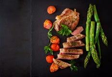 Juicy μέσο σπάνιο βόειο κρέας μπριζόλας με τα καρυκεύματα και τις ντομάτες, σπαράγγι στοκ εικόνα