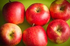Juicy μήλα σε ένα πράσινο υπόβαθρο Στοκ εικόνα με δικαίωμα ελεύθερης χρήσης