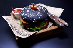 Juicy μαύρο burger Burger με το μαρμάρινο βόειο κρέας, δίκρανο με το μαχαίρι και σάλτσα τσίλι Στοκ Φωτογραφίες