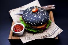 Juicy μαύρο burger Burger με το μαρμάρινο βόειο κρέας, δίκρανο με το μαχαίρι και σάλτσα τσίλι Στοκ Εικόνα