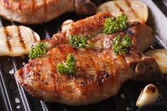 Juicy μπριζόλα χοιρινού κρέατος που ψήνεται στη σχάρα με τα κρεμμύδια σε μια παν κινηματογράφηση σε πρώτο πλάνο σχαρών Στοκ εικόνα με δικαίωμα ελεύθερης χρήσης