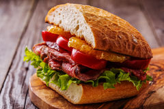 Juicy σάντουιτς μπριζόλας με τα λαχανικά και τις φέτες του πορτοκαλιού Στοκ φωτογραφία με δικαίωμα ελεύθερης χρήσης