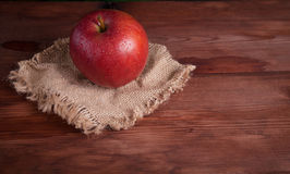 Juicy apple on a wood desk. And burlap Stock Photos